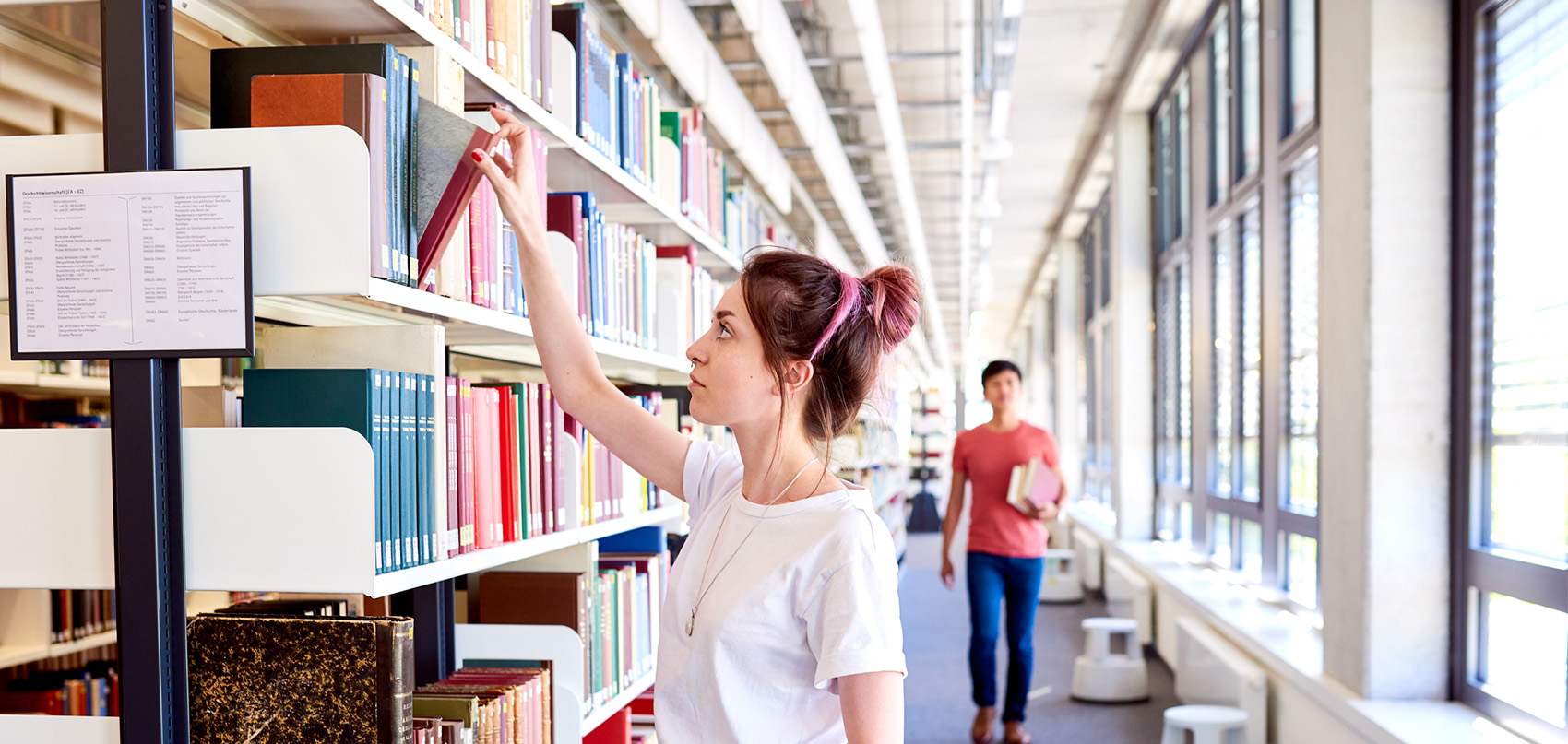 A students takes a book out of the library's shelf