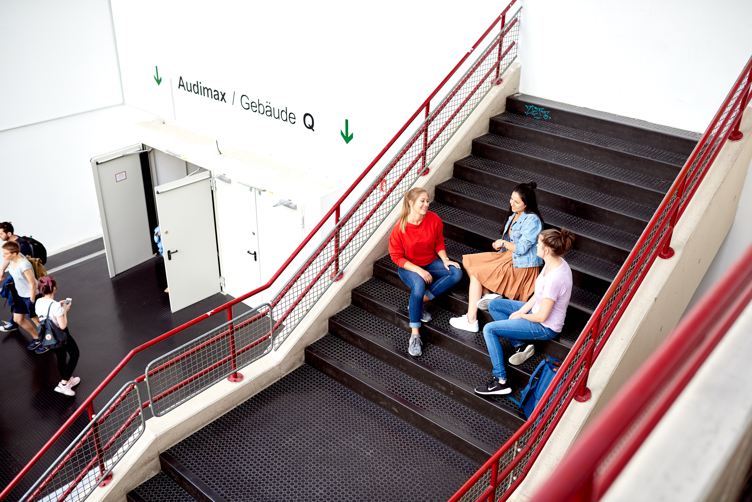 Students sitting on stairs next to the Audimax